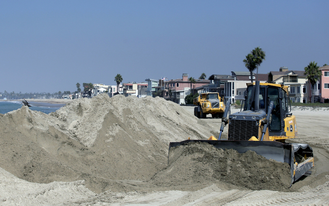 A bulldozer works to pile sand on a temporary berm to protect beach front homes on, Friday, Sept. 5, 2014, in Long Beach, Calif. Southern California is in for another round of high surf generated  ...