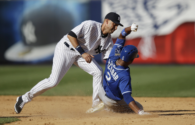 New York Yankees shortstop Derek Jeter (2) tags Kansas City Royals Alcides Escobar (2) after Escobar was caught stealing in the ninth inning of in a baseball game at Yankee Stadium in New York, Su ...