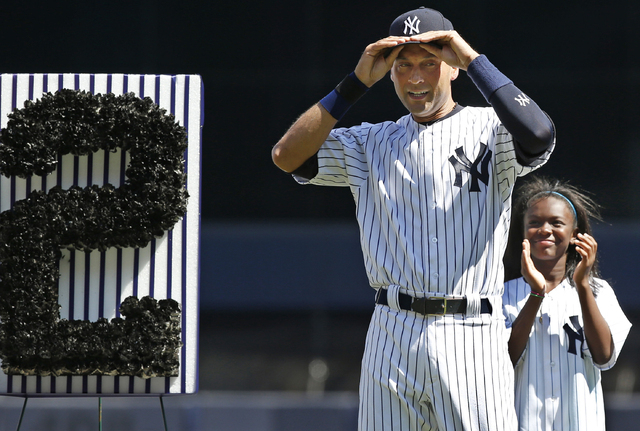 A youngster applauds as New York Yankees shortstop Derek Jeter (2) adjusts his cap after tipping it to the crowd during a pregame ceremony honoring the Yankees captain who is retiring at the end o ...