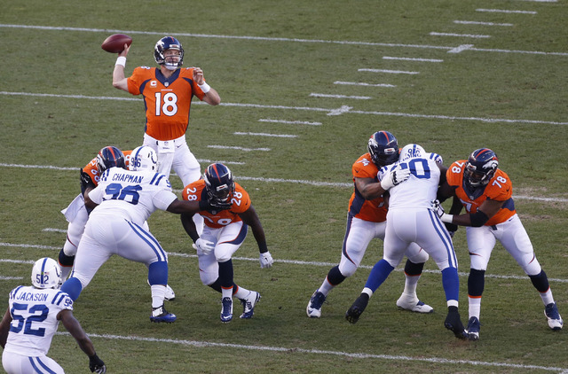Denver Broncos quarterback Peyton Manning (18) throws against the Indianapolis Colts during the first half of an NFL football game, Sunday, Sept. 7, 2014, in Denver. (AP Photo/Brennan Linsley)