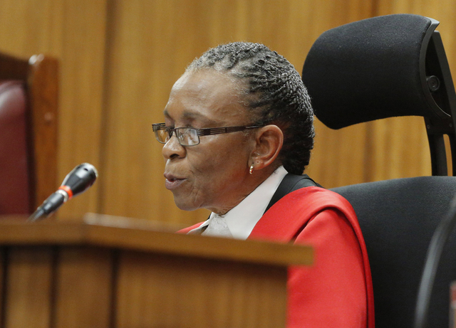 Judge Thokozile Masipa reads notes as she delivers her verdict in the Oscar Pistorius murder trial, in Pretoria, South Africa, Thursday, Sept. 11 2014. The verdict is expected to take hours and po ...