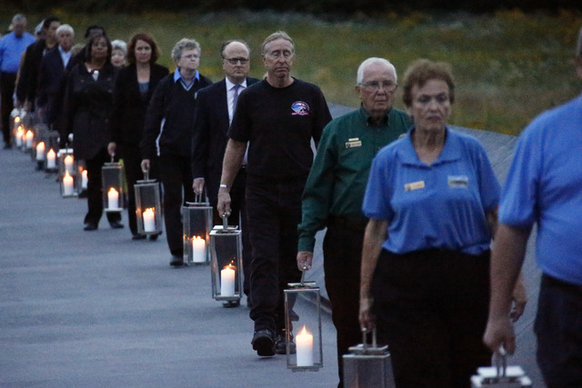 Candles in memory of the 40 passengers and crew of Flight 93, are carried to the Wall of Names at the Flight 93 National Memorial in Shanksville, Pennsylvania, on Wednesday, Sept. 10, 2014. Thursd ...