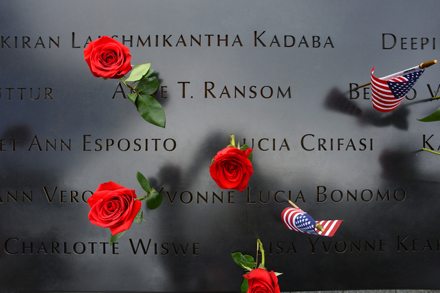 Roses and flags left by loved ones are placed on the names inscribed at the North Pool during memorial observances on the 13th anniversary of the Sept. 11 terror attacks on the World Trade Center  ...
