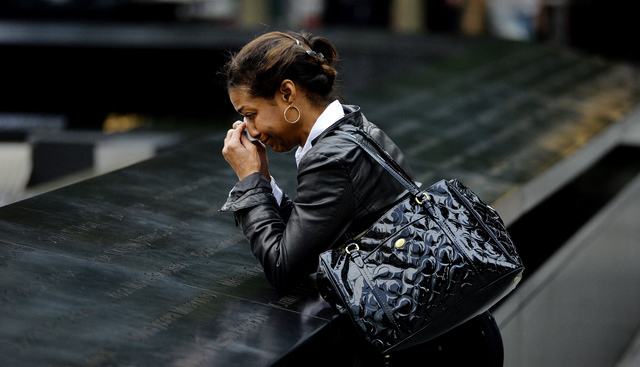 A woman pauses at the edge of the North Pool during memorial observances on the 13th anniversary of the Sept. 11 terror attacks on the World Trade Center in New York, Thursday, Sept. 11, 2014.   I ...