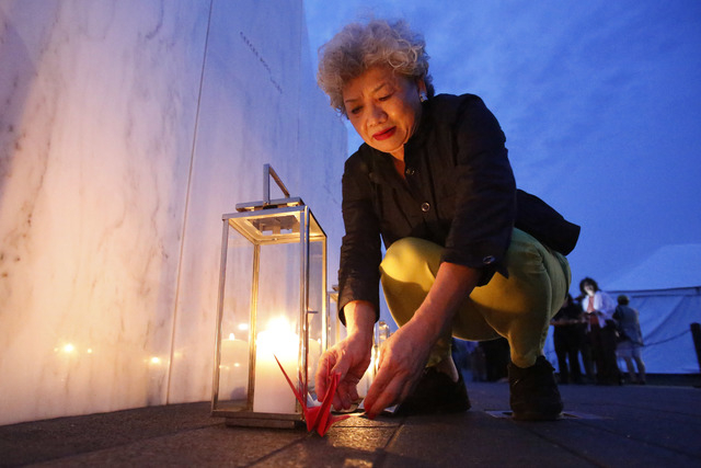 Yachiyo Kuge, the mother of Toshiya Kuge who was a passenger on Flight 93, places origami birds near his name, at the Wall of Names at the Flight 93 National Memorial in Shanksville, Pennsylvania, ...