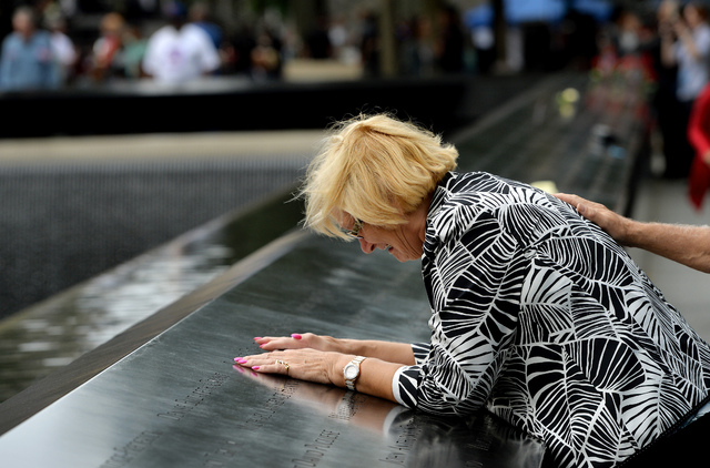 Paola Braut, of Belgium, cries over a photograph of her son Patrice along the edge of the North Pool during memorial observances on the 13th anniversary of the Sept. 11 terror attacks on the World ...