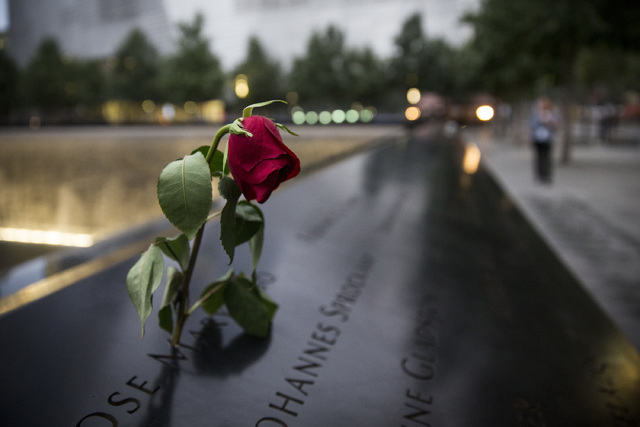 A wilting rose is left in remembrance of those lost before the memorial observances held at the site of the World Trade Center in New York, Sept. 11, 2014. This year marks the 13th anniversary of  ...