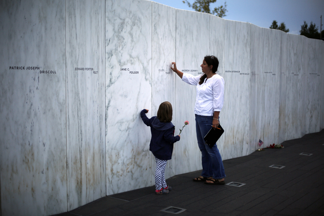 Visitors to the Flight 93 National Memorial in Shanksville, Pennsylvania, on Wednesday, Sept. 10, 2014, touch the Wall of Names. The memorial marks the spot where United Airlines Flight 93 crashed ...