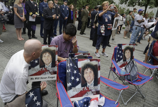 Brian Sommer, left, and Lito Deleon hold photos of their friend Wayne Russo, who died in the Sept. 11, 2001, attacks, during memorial observances held at the site of the World Trade Center in New  ...