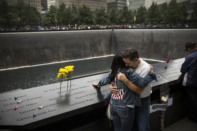 Eileen Esquilin hugs her husband, Joe Irizarry, while mourning the loss of her brother, Ruben Esquilin Jr., during memorial observances on the 13th anniversary of the Sept. 11 terror attacks on th ...