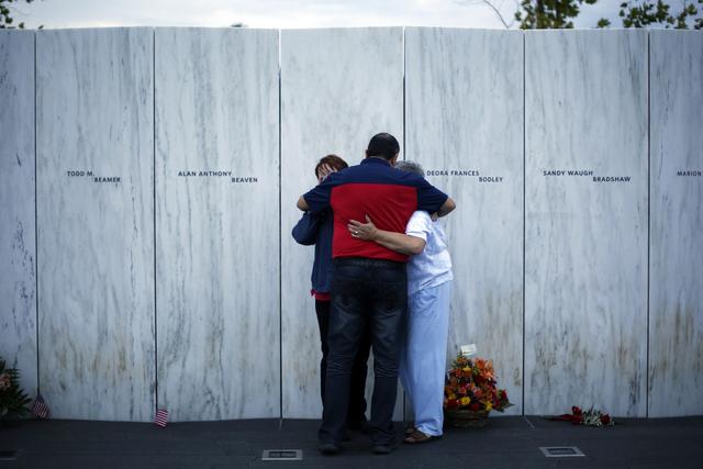Rick Sarmiento, center, embraces Karen Bingham, left, and Nancy Root, right, during a visit to the Flight 93 National Memorial on Wednesday, Sept. 10, 2014, Shanksville, Pennsylvania. Karen Bingha ...