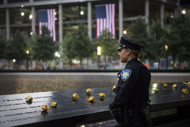 Port Authority Police Officer Donna Przybyszewski takes a moment to herself before family members are let in for the memorial observances held at the site of the World Trade Center in New York, Se ...