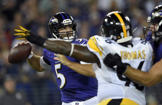 Baltimore Ravens quarterback Joe Flacco (5) looks to pass under pressure from Pittsburgh Steelers nose tackle Cam Thomas (96) during the first half of an NFL football game Thursday, Sept. 11, 2014 ...