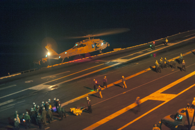 This photo provided by the US Navy, a MH-60S Sea Hawk helicopter lands on the flight deck of the Nimitz-class aircraft carrier USS Carl Vinson (CVN 70) during search and rescue operations for a mi ...