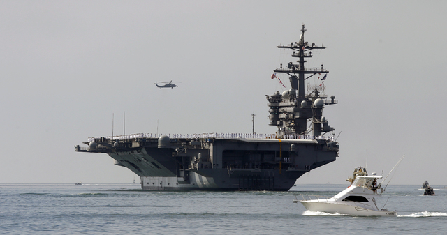 FILE-This Friday, Aug. 22, 2014 file photo the aircraft carrier USS Carl Vinson sails out of San Diego Harbor leaving for a nine month deployment in San Diego. Two U.S. Navy jets crashed into the  ...