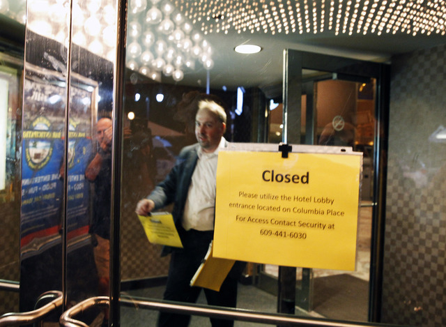 A worker posts closed signs on the lobby doors at Trump Plaza Hotel & Casino early Tuesday, Sept. 16, 2014, in Atlantic City, N.J. in Atlantic City, N.J. The hotel and casino closed its doors earl ...