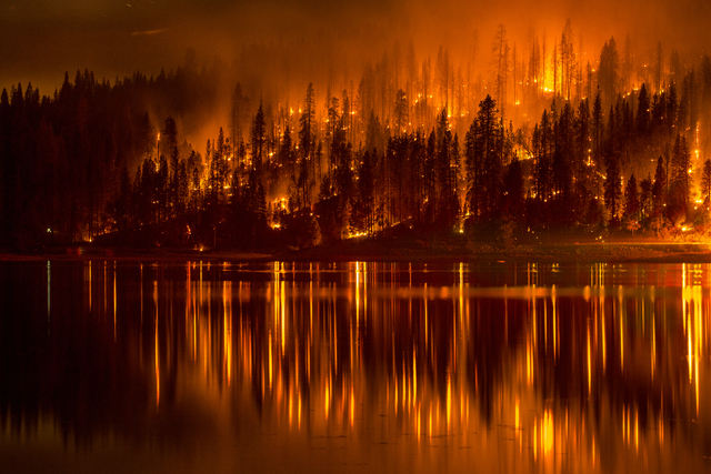 This Sunday, Sept. 14, 2014, photo shows fire as it approaches the shore of Bass Lake, California. Crews are attempting to get better access to two raging wildfires in California that have forced  ...