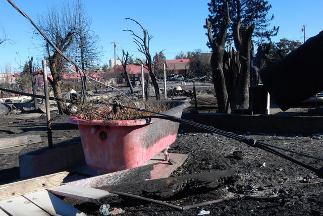 A bathtub is seen painted pink with fire retardant, Tuesday, Sept. 16, 2014, in the rubble of a home destroyed by a wildfire in Weed, California. The fast-moving fire leveled approximately 100 str ...
