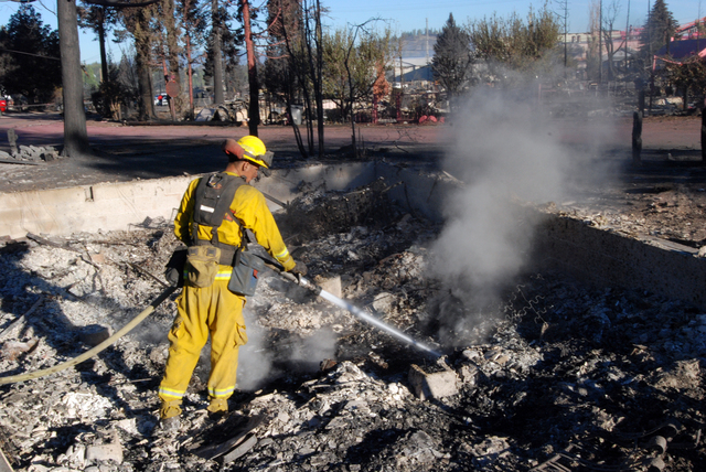 A firefighter hoses down smoking rubble, Tuesday, Sept. 16, 2014, inside the foundation of a home destoyed by a wildfire in Weed, California. The fire moved quickly after igniting Monday afternoon ...