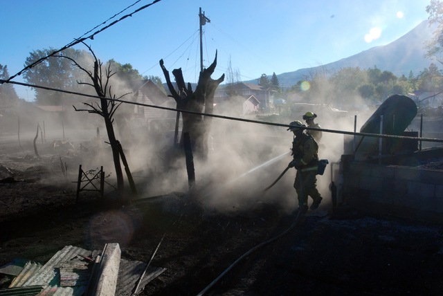 Firefighters hose down the smoldering remains of a home Tuesday, Sept. 16, 2014, in Weed, California. A fast-moving wildfire destroyed at least 100 structures before winds died down and firefighte ...