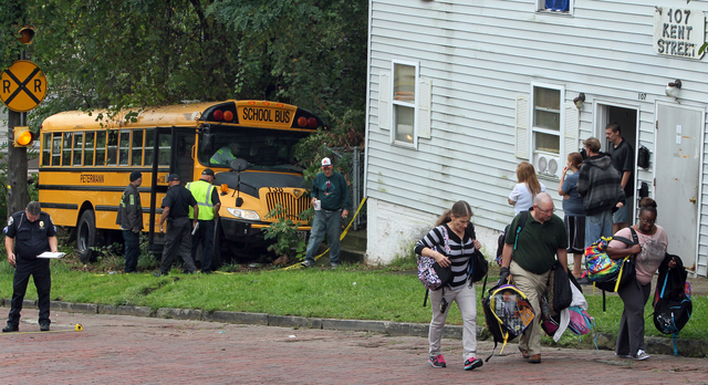 Student book bags are removed from the scene of an accident on Tuesday, Sept. 16, 2014, in Akron, Ohio. Police say a school bus driver was killed when the bus rolled over her during an evacuation  ...
