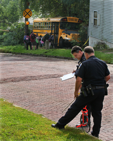 Akron police work at the scene of an accident involving a school bus on Tuesday, Sept. 16, 2014, in Akron, Ohio.  Police say a school bus driver was killed when the bus rolled over her during an e ...
