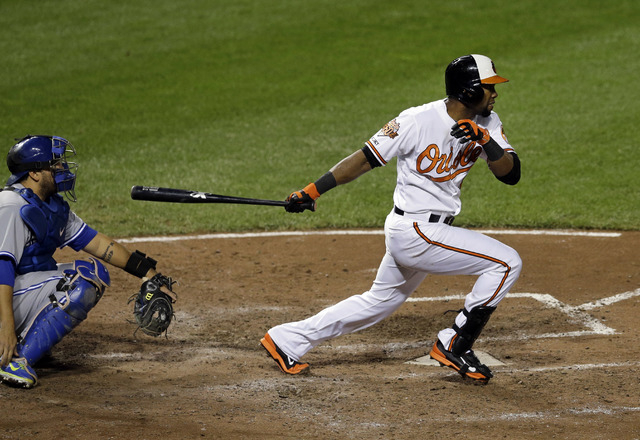 Baltimore Orioles' Alejandro De Aza watches his three-run triple in front of Toronto Blue Jays catcher Dioner Navarro in the seventh inning of a baseball game, Tuesday, Sept. 16, 2014, in Baltimor ...