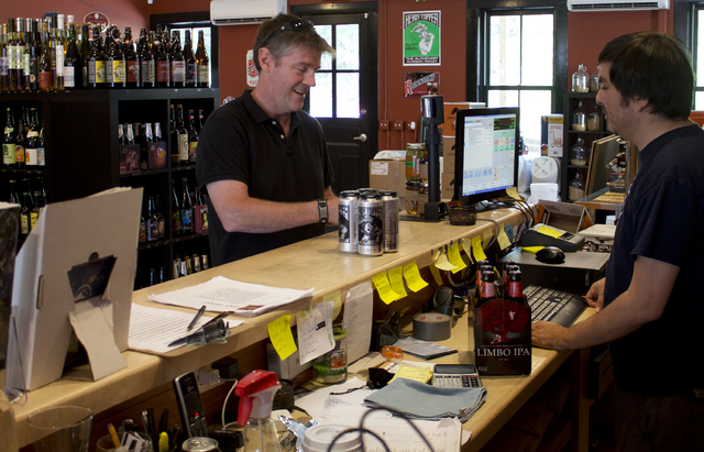 In this Sept. 11, 2014 photo, Tom Owens of Marion, Mass., left, buys Heady Topper from sales clerk Victor Osinaga at Craft Beer Cellar in Waterbury, Vt. Owens traveled to Vermont in order to buy t ...