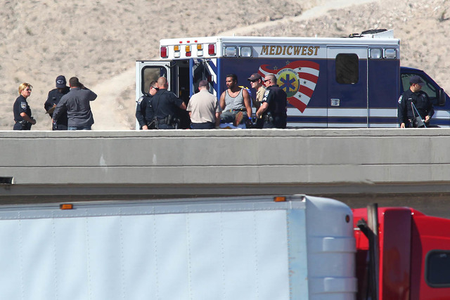 The man who threatened to harm himself is seen on a gurney with Nevada Highway Patrol and North Las Vegas police officers, along with negotiators, on the I-15 at the Las Vegas Boulevard exit, nort ...