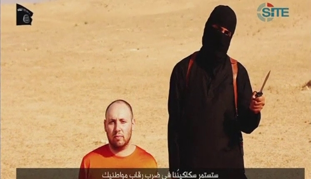 A video purportedly showing U.S. journalist Steven Sotloff kneeling next to a masked Islamic State fighter holding a knife in an unknown location in this still image from video released by Islamic ...