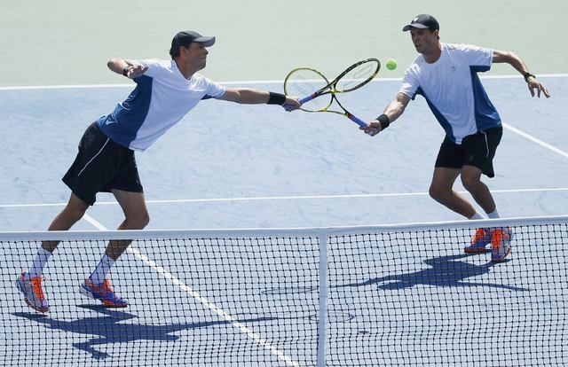 Bob Bryan (L) and his brother Mike Bryan of the U.S. reach for the ball while playing Marcel Granollers and Marc Lopez of Spain during their men's doubles final match at the 2014 U.S. Open tennis  ...