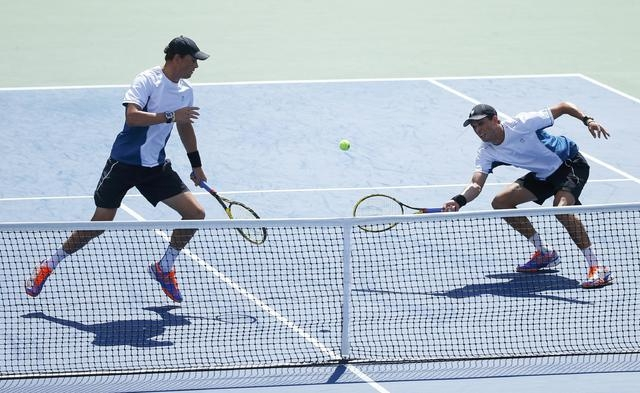 Bob Bryan (L) of the U.S. watches as his brother Mike Bryan returns the ball to Marcel Granollers and Marc Lopez of Spain during their men's doubles final match at the 2014 U.S. Open tennis tourna ...