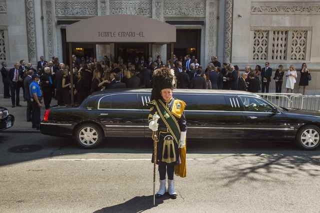 A member of a bagpipe ensemble looks on as mourners depart the funeral of comedian Joan Rivers at Temple Emanu-El in New York September 7, 2014. REUTERS/Lucas Jackson (UNITED STATES - Tags: ENTERT ...