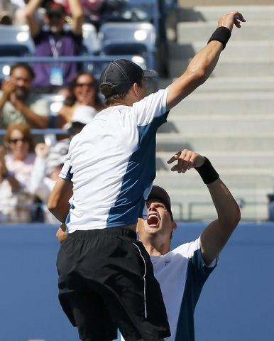 Bob Bryan (rear) and his brother Mike Bryan of the U.S. celebrate after defeating Marcel Granollers and Marc Lopez of Spain in their men's doubles final match at the 2014 U.S. Open tennis tourname ...