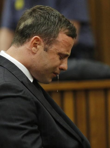 Olympic and Paralympic track star Oscar Pistorius reacts as he listens to Judge Thokozile Masipa's judgment at the North Gauteng High Court in Pretoria, Thursday, Sept. 11, 2014. A South African j ...