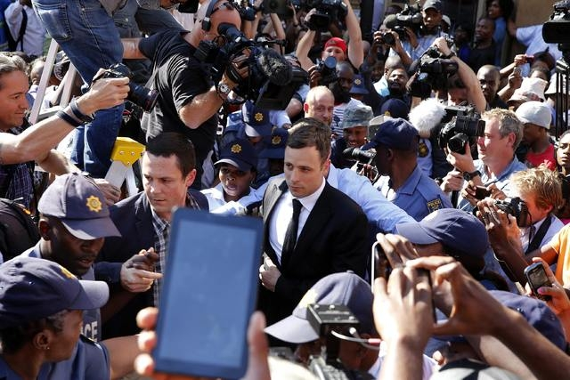 Paralympic track star Oscar Pistorius, center, leaves after hearing the verdict of his trial at the high court in Pretoria, Thursday, Sept. 11, 2014. A South African judge cleared Pistorius of all ...