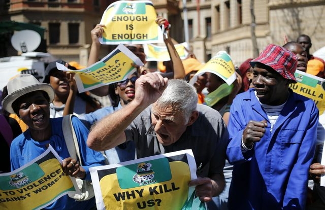 Protesters chant slogans as they hold placards outside the high court in Pretoria on Thursday, Sept. 11, 2014. A South African judge cleared Oscar Pistorius of all murder charges on Thursday, sayi ...