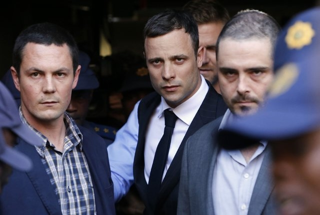 South African Olympic and Paralympic sprinter Oscar Pistorius, center, leaves the North Gauteng High Court in Pretoria, Thursday, Sept. 11, 2014. A South African judge cleared Pistorius of all mur ...