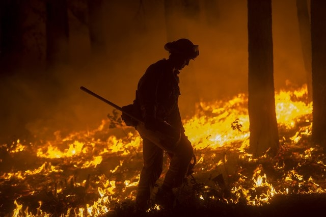 A firefighter crosses a backfire while battling the King Fire in Fresh Pond, California, Wednesday, Sept. 17, 2014. Fire crews in California's rugged Sierra Nevada are trying to gain the upper han ...