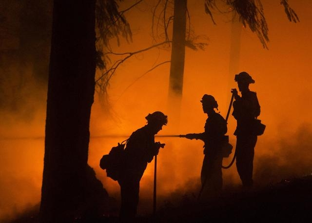Firefighters battle the King Fire in Fresh Pond, California, Wednesday, Sept. 17, 2014. Fire crews in California's rugged Sierra Nevada are trying to gain the upper hand in a blaze that threatened ...