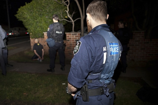 An Australian Federal Police officer, front, and a New South Wales policeman stand near a suspect, left, who was detained during a raid on a house in western Sydney, Thursday, Sept. 18, 2014. Inte ...
