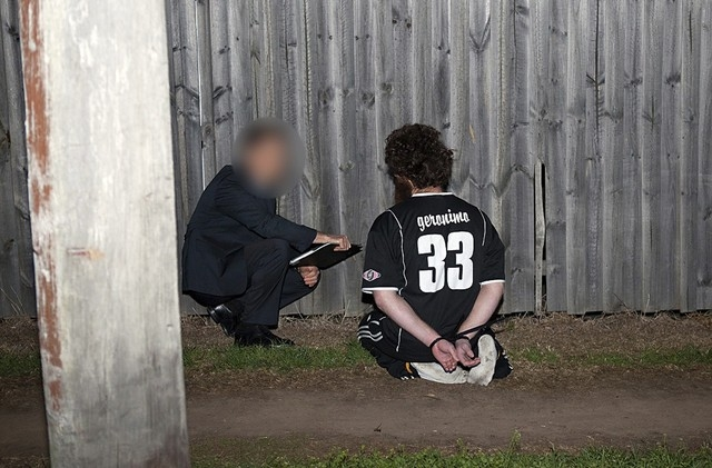 An Australian Federal Police officer, left, talks with a suspect who was detained during a raid on a house in western Sydney, Thursday, Sept. 18, 2014. Intelligence showed that militants connected ...