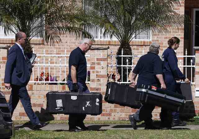 Members of the Australian Federal Police forensic unit carry equipment into a house that was involved in pre-dawn raids in the western Sydney suburb of Guilford, Thursday, Sept. 18, 2014. (Reuters ...