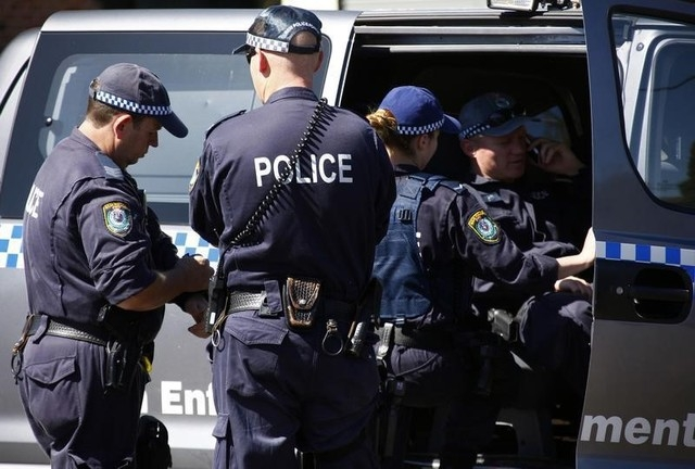 Police talk outside a house that was involved in pre-dawn raids in the western Sydney suburb of Guilford, Thursday, Sept. 18, 2014. Intelligence showed that militants connected with radical group  ...