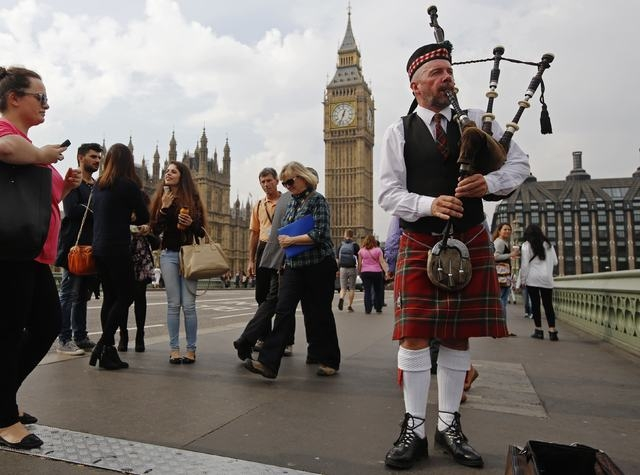 Piper Anton Doherty plays to passers-by in front of the Houses of Parliament on Westminster Bridge in London, Thursday, Sept. 18, 2014. Polling in the referendum on Scottish independence began on  ...
