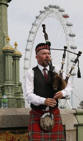 Piper Anton Doherty plays to passers-by in front of the London Eye on Westminster Bridge in London, Thursday, Sept. 18, 2014. Polling in the referendum on Scottish independence began on Thursday m ...