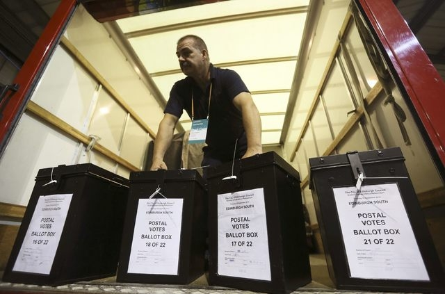 A man carries ballot boxes at a counting centre in Edinburgh, Scotland, Thursday, Sept. 18, 2014. Scotland voted on Thursday on whether to stay within the United Kingdom or end the 307-year-old un ...