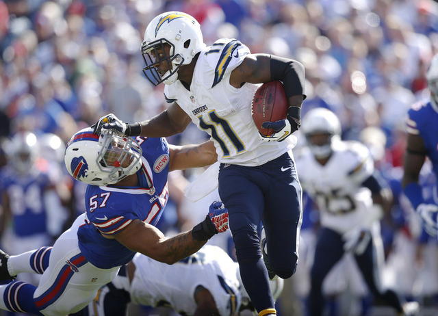 Sep 21, 2014; Orchard Park, NY, USA; San Diego Chargers wide receiver Eddie Royal (11) stiff arms Buffalo Bills linebacker Ty Powell (57) on a run during the second half at Ralph Wilson Stadium. C ...