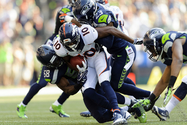 Sep 21, 2014; Seattle, WA, USA; Denver Broncos wide receiver Emmanuel Sanders (10) carries the ball while being tackled by Seattle Seahawks linebacker Kevin Pierre-Louis (58) and Seattle Seahawks  ...