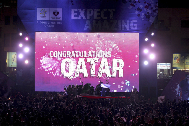 "People celebrate in front of a screen that reads ""Congratulations Qatar"" after FIFA announced that Qatar will be host of the 2022 World Cup in Souq Waqif in Doha, in this December 2, 2010 file pic ..."